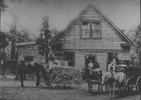 old black and white photo with horse carriages out front