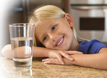 girl with head on arms smiles at glass of clear water